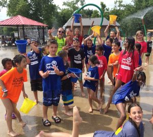 Group of campers and counselors smiling and posing at splashpad