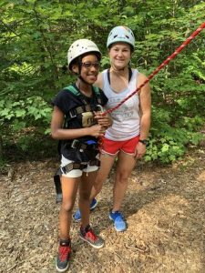 Camper and counselor posing wearing rock climbing equipment