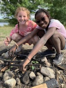 Campers smiling in front of their campfire pit