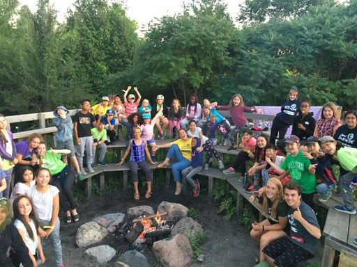 Group of campers and counselors smiling around fire pit